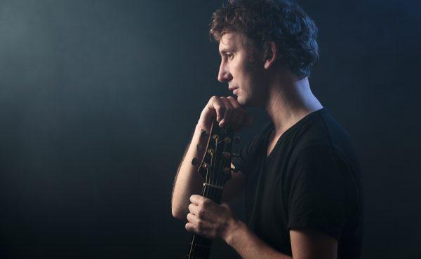 Retrato del músico Guillem Mitchel con su guitarra